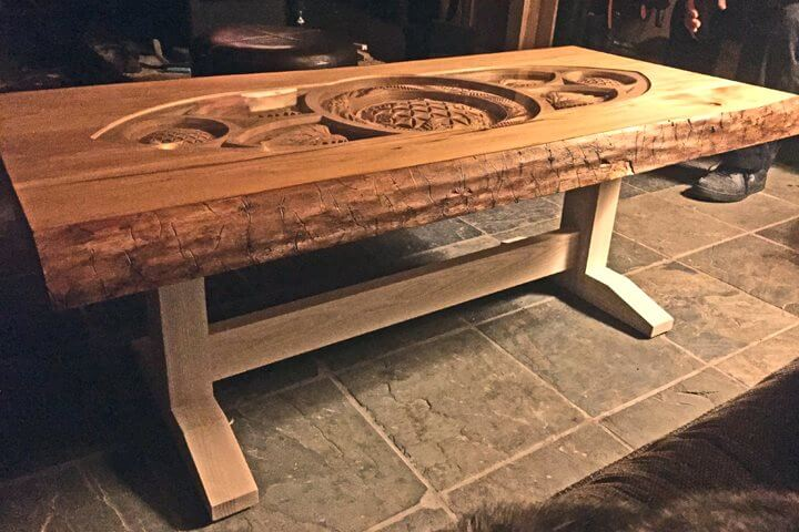 A custom live-edge coffee table with deep carvings covered by glass flush to the wooden table surface.